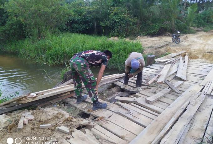 Babinsa Memperbaiki Jembatan Yang rusak Bersama Masyarakat.