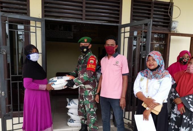 Bulan Ramadhan, Babinsa Koramil 16/Tapung Bantu Pemerintah Desa Bagikan Beras Raskin