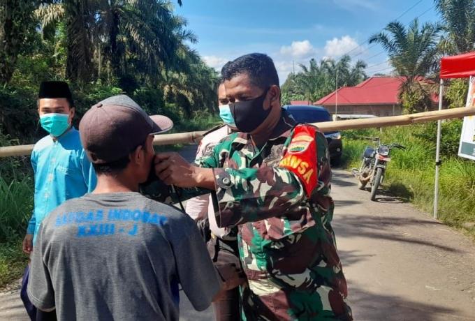 Himbau Masyarakat Patuhi Protokol Kesehatan Babinsa Bagikan Masker di Jalan Poros