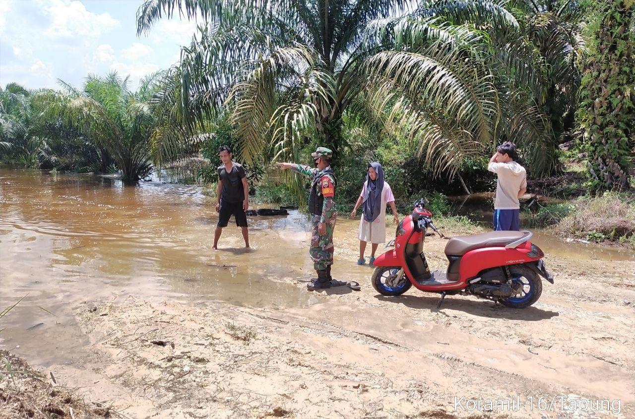 Jalan Terendam Banjir Babinsa Koramil 16/Tapung Bantu Alihkan Pengendara Ke Jalan Alternatif