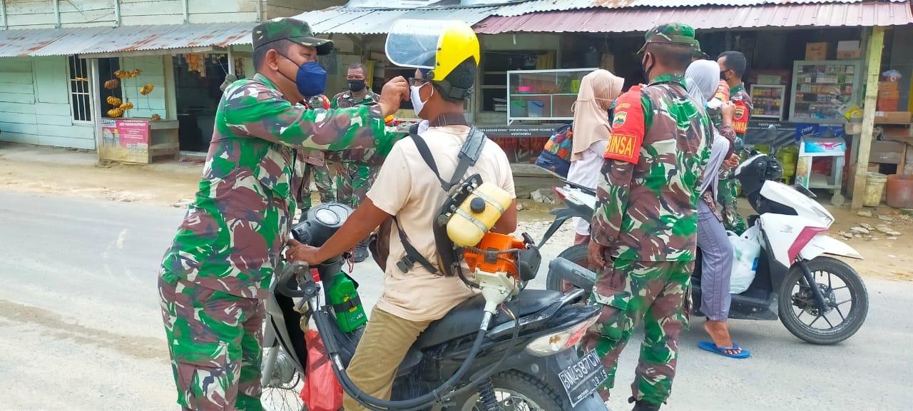 Personel Babinsa Koramil 15/Kuala Kampar Bagikan Masker Kepada Pengguna Jalan