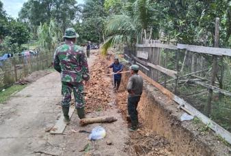 Babinsa dan Masyarakat Membaur Untuk Merapikan Lubang Yang Digali Untuk Pembuatan Drainase.